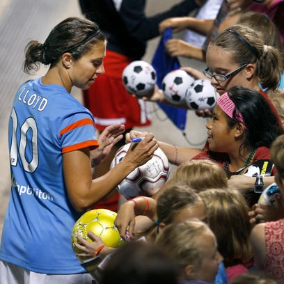 Houston's Carlie Lloyd signs autographs for fans after