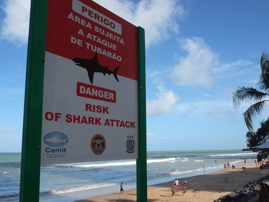 In this June 15, 2014, photo, a sign warns of the danger sharks pose to swimmers at Boa Viagem beach in Recife, Brazil. The beach, which has seen an influx in visitors during the World Cup, has had more reported shark attacks than any other beach in Brazil. According to the state's Shark Incident Monitoring Committee, 59 people have been attacked by sharks in or near Recife since 1992. Some tourists' eyes widen as they notice the shark symbol while approach the huts to order Brazilian cocktails. (AP Photo/Lawrence Rincon)