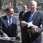 Sen. Patrick Leahy, D-Vt., right, holds a model airplane from Bob Deluce, left, president of Porter Airlines, outside the Amtrak station in Essex Junction. At rear is Vermont Transportation Secretary Chris Cole. The officials were highlighting progress in Congress to expand the use of pre-clearing people to enter the United States from Canada by rail and air.