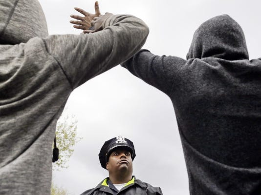 A member of the Baltimore Police Department stands guard outside of the department's Western District police station as men hold their hands up in protest Wednesday during a march for Freddie Gray, in Baltimore.