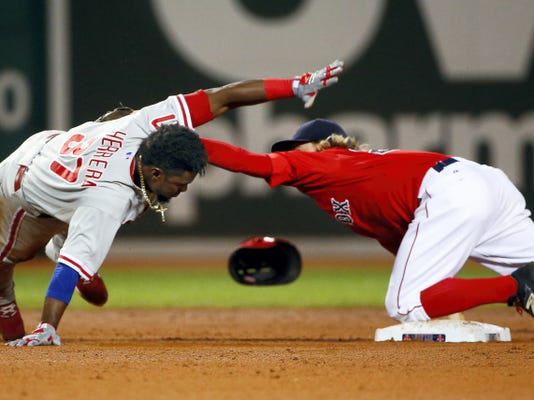Philadelphia Phillies' Odubel Herrera (37) is tagged out by Boston Red Sox second baseman Brock Holt after he missed the bag while trying to stretch a single into a double during the fifth inning of Friday's game at Fenway Park.