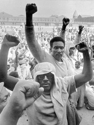 Inmates of Attica state prison in upstate New York raise their fists to show solidarity in their demands during a negotiation session with state prisons Commissioner Russell Oswald, in this Sept. 10, 1971, file photo.