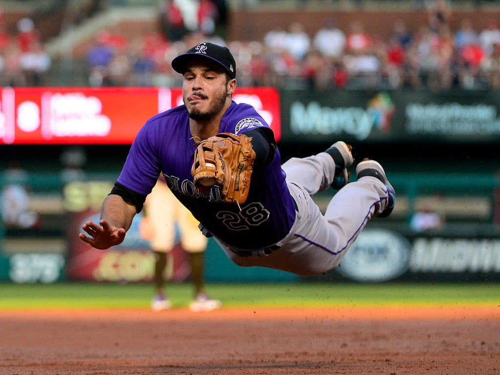 Colorado Rockies third baseman Nolan Arenado dives and catches a line drive hit by St. Louis Cardinals second baseman Kolten Wong during the first inning at Busch Stadium in St. Louis.