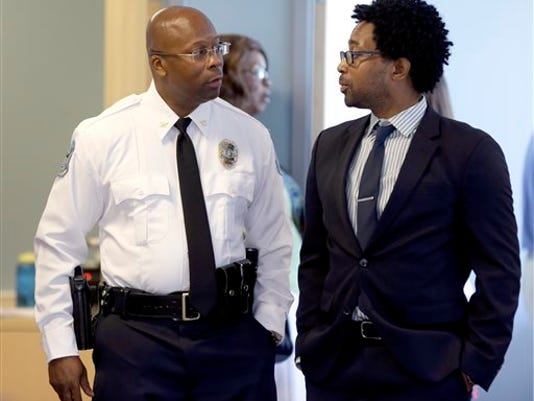 Andre Anderson speaks with Ferguson City Council member Wesley Bell, right, after being introduced as the the interim chief of the Ferguson Police Department during a news conference Wednesday, July 22, 2015, in Ferguson, Mo. Anderson becomes the second interim chief since Police Chief Thomas Jackson stepped down in March.