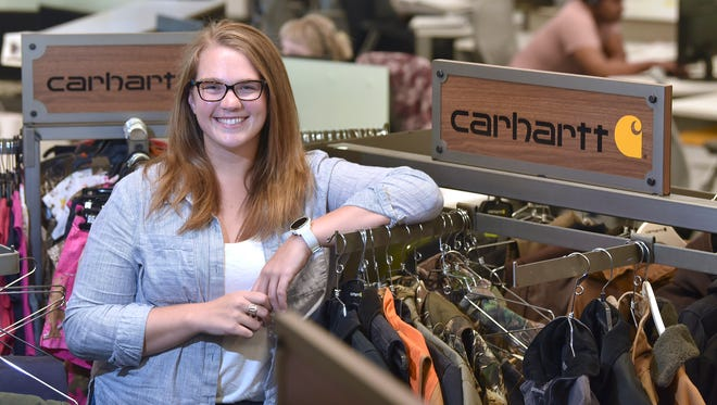 Carhartt Sales Operations Specialist Emily Willer, 26, of Royal Oak, poses among merchadise near the customer engagement department at Carhartt World Headquarters in Dearborn on July 27. Willer, a U-M graduate with psychology and spanish degrees, is part of Carhartt's student loan repayment assistance plan with a monthly reimbursement of $50 up to $10,000.