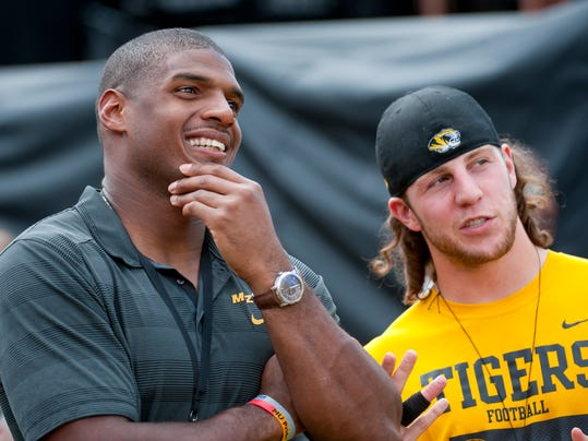 Former Missouri player Michael Sam talks with former teammate T.J. Moe before the start of the South Dakota State-Missouri NCAA college football game Saturday, Aug. 30, 2014, in Columbia, Mo. Sam, the first openly gay player drafted by an NFL team, was released by St. Louis Rams Saturday.(AP Photo/L.G. Patterson)
