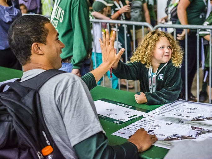 Kennedy Drake,4, high fives MSU quarterback Damion Terry during the 2014 version of Meet the Spartans Tuesday August 12, 2014 at Spartan Stadium in East Lansing.