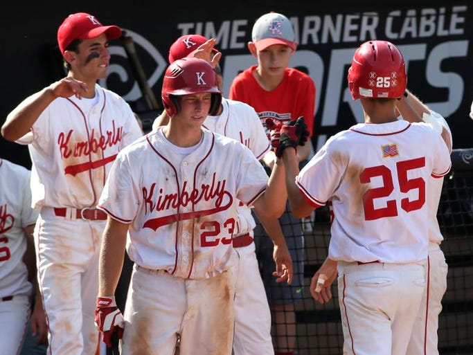 Kimberly High Schoolâ??s players celebrate a run scored by Danny VandenBoom (25) against Hartford Union High School during their WIAA Division 1 quarterfinal state baseball tournament game, Tuesday June16, 2014, at Grand Chuteâ??s Neuroscience Group Field at Fox Cities Stadium, Wis.