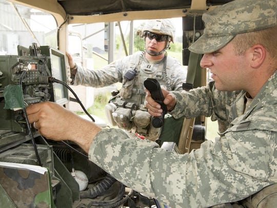 Capt. Gary Clark, of Syracuse, background, listens as Spc. Ethan Scott of Slaterville Springs, explains the temporary repair he has made to the radio in the captain's Humvee.