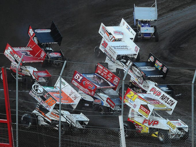 Drivers pass the starting line in a World of Outlaws sprint car race at Huset's Speedway on Wednesday, July 2, 2014.