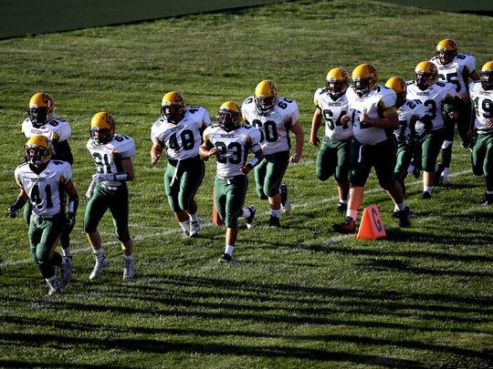 The Little Miami football team runs onto the field