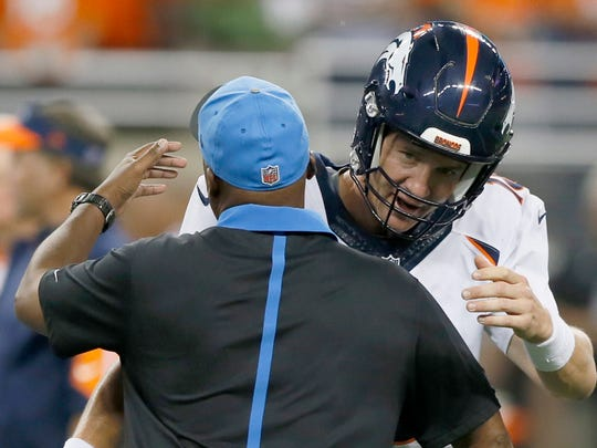 Denver Broncos quarterback Peyton Manning and Detroit Lions head coach Jim Caldwell give each other a hug as they finish a conversation at midfield before the Lions Broncos football game.