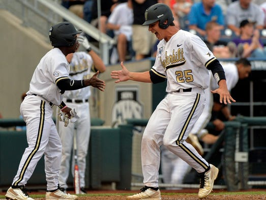 Vanderbilt's Karl Ellison (25) is greeted by teammate Ro Coleman, left, after scoring on a two-run double by Dansby Swanson in the second inning Saturday.