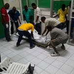 The body of a person killed during carnival celebrations is moved at the General Hospital in Port-au-Prince, Haiti, early Tuesday, Feb. 17, 2015. At least 20 people on a music group's packed Carnival float in the Haitian capital were killed Tuesday when they were electrocuted by a power line, officials said.
