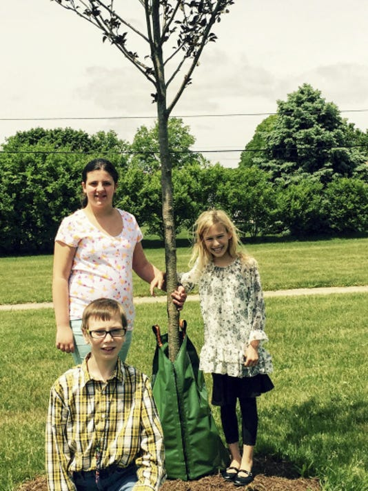 Blain Wood, front, Maddie Boltz, left, and Abby Foutz pose by a tree planted recently at Forge Road Elementary School in Palmyra.