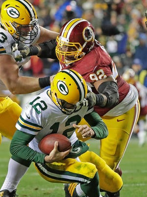 Green Bay Packers quarterback Aaron Rodgers (12) gets sacked by defensive end Chris Baker (92) against the Washington Redskins at Fedex Field on Nov. 20, 2016.