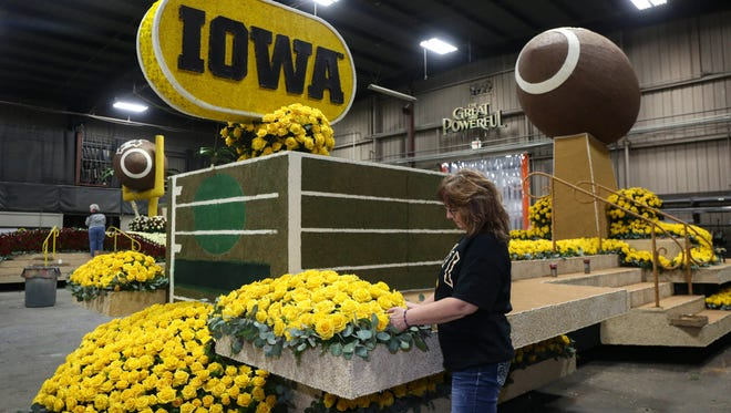 Tonya Warnell, a florist from Marshalltown, makes some final adjustments to the Iowa Hawkeye float on Wednesday, Dec. 30, 2015, in Azusa, Calif.