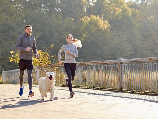 happy couple with dog running outdoors