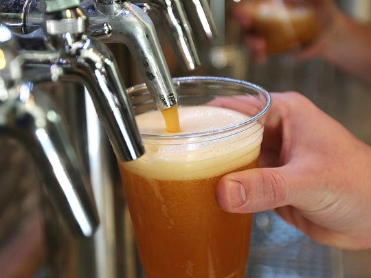 One of the homemade brews is poured into a glass at Proof Brewing Company.