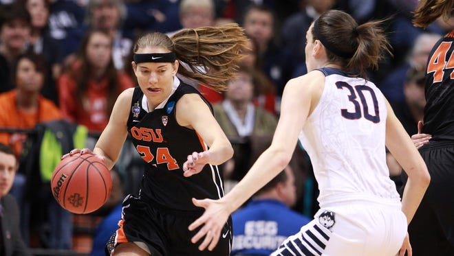 Oregon State guard Sydney Wiese (24) dribbles the ball as Connecticut forward Breanna Stewart (30) defends during the first quarter of the Final Four game Sunday in Indianapolis. UConn won 80-51.