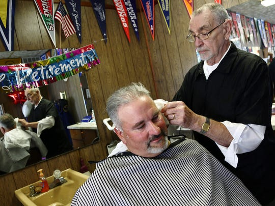 Al Phillips gets a trim Friday afternoon from Hank Hall. Hall is retiring after 61 years as a barber.