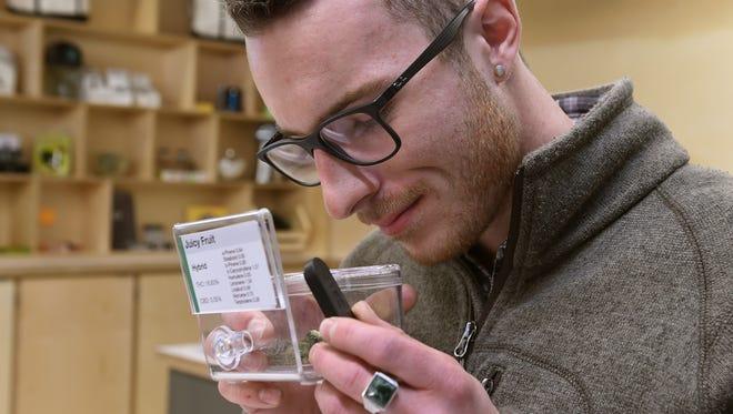 Customer Ben Crowley smells a sample of marijuana at the Sierra Wells marijuana dispensary in Reno on Thursday Jan. 4, 2018.
