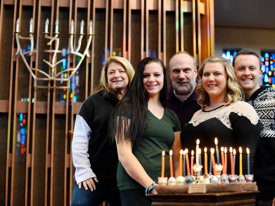 Harla Verman, left, and Eric Verman, center, with their daughters, Jayme Verman, second from left, Bari Verman, second from right, and Bari's fiancee, Michael Dixon, stand behind the family's Noah's Ark-themed menorah at Temple Beth Israel in York Township.