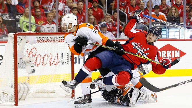 Apr 22, 2016; Washington, DC, USA; Philadelphia Flyers defenseman Samuel Morin (55) checks Washington Capitals center Marcus Johansson (90) into Flyers goalie Michal Neuvirth (30) in the first period in game five of the first round of the 2016 Stanley Cup Playoffs at Verizon Center. Mandatory Credit: Geoff Burke-USA TODAY Sports