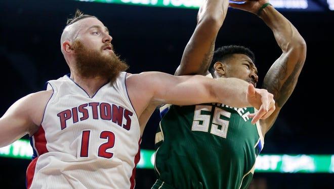 The Milwaukee Bucks' Orlando Johnson grabs a rebound away from the Detroit Pistons' Aron Baynes, left, on Monday, Oct. 17, 2016, in Auburn Hills.
