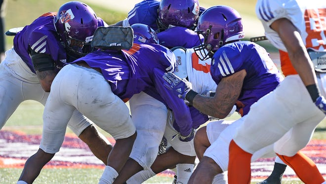 Northwestern State defenders make a tackle during Thursday's scrimmage.
