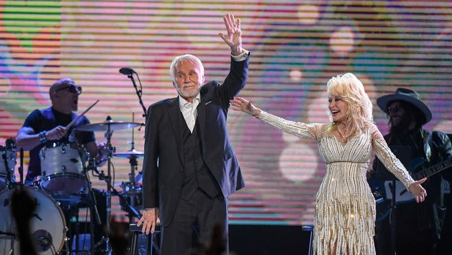 "Kenny Rogers and Dolly Parton wave goodbye to the crowd after performing for the last time at the ""All In For the Gambler"" tribute to Rogers at Bridgestone Arena in Nashville on Oct. 25, 2017."