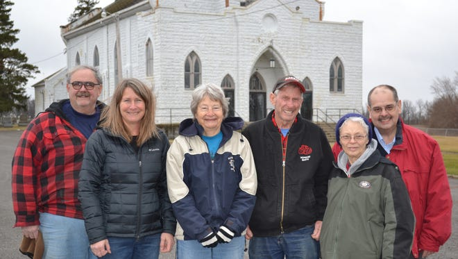 Former members of St. Sebastian stand in front of the church, which will likely be razed in the near future by the Diocese of Toledo. The group is leading efforts to purchase the church from  the diocese with hopes to turn it into a museum. Pictured are, left to right, Steve Bischoff, Deb Bumb, Sharon Smith, Howard Smith, Joan Schaffer and John Elmlinger.