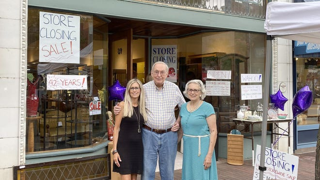 Richard and Jackie Pope, owners of The Glass Menagerie, and their daughter, Melissa Fox, stand in front of the business, which will soon be closed after 42 years of service to the community.