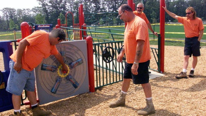 Workers check a Jackson Township playground designed for children with special needs in this 2004 file photo.