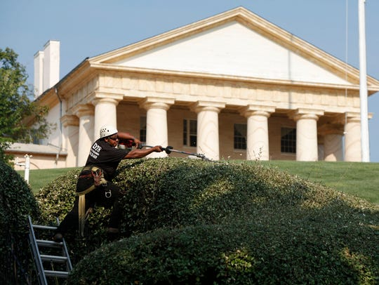 A worker trims the hedges at Arlington National Cemetery.