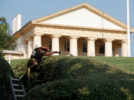 A worker trims the hedges at Arlington National Cemetery. Shown in the rear is Arlington House, the former home of Robert E. Lee, now a national memorial to him.