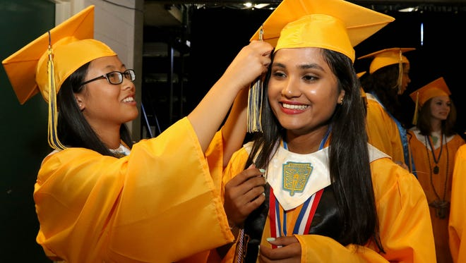 (l) Stephanie Tu helps classmate Sheryl Dalal with her tassel before the start of the graduation ceremony for Franklin High School held at Sun National Bank Center in Trenton, June 26, 2015. Mary Iuvone/For The Home News
