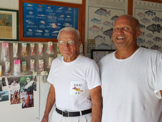 Donald Podany, left, and Capri fishing buddy Dave Rizzo stand in front of Podany's custom-made fishing lures and wall of fame.
