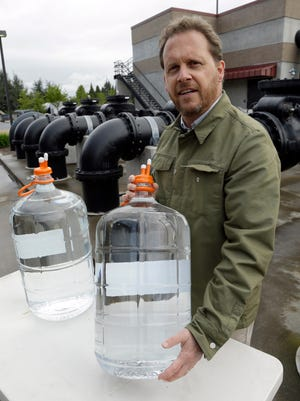 In this photo taken on Friday, April 24, 2015, Clean Water Services spokesperson Mark Jockers shows sealed containers of highly purified water from their facility in Forest Grove, Ore.  The utility plans to release 300 gallons of  the highly purified water next month to roughly 20 home brewers from the Oregon Brew Crew, the state's oldest home-brewing club.  A panel of experts will judge the beers in July, and the best kegs will be taken to an international water conference in Chicago. (AP Photo/Don Ryan)