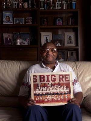 Bobby Kelly, former Bengal and retired Hughes High School coach for 27 years holds a picture of one of his Big Red football teams in his West Side home in 2002. Kelly died last Thursday.