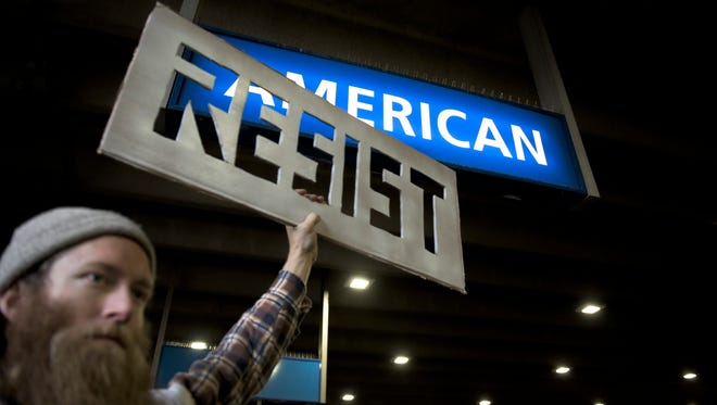 A protestor rallies under an American Airlines arrival gate at Philadelphia International Airport Sunday, Jan. 29, 2017 in Philadelphia.