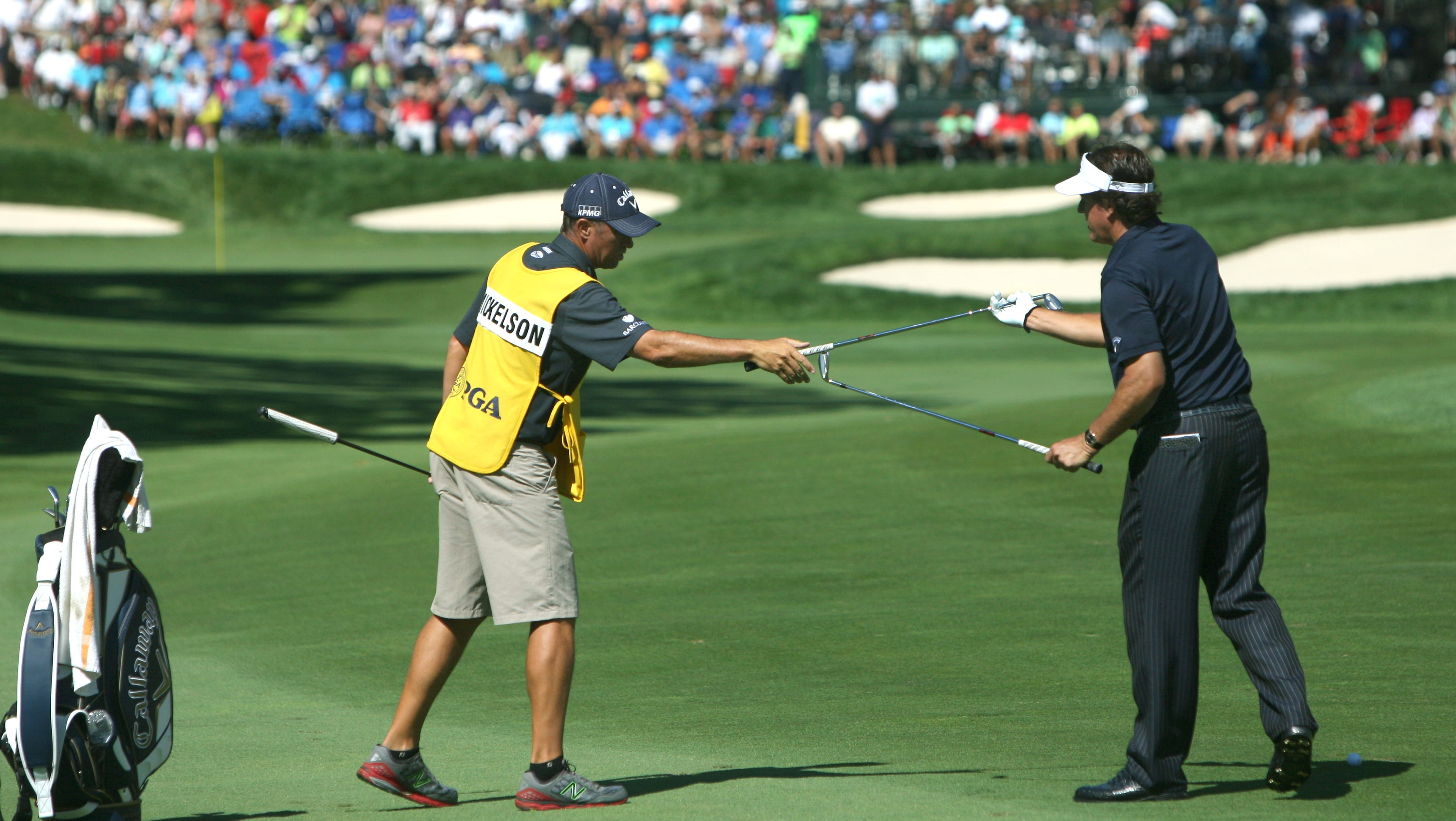 Phil Mickelson exchanges clubs with his caddie before swinging towards the green on 13.
