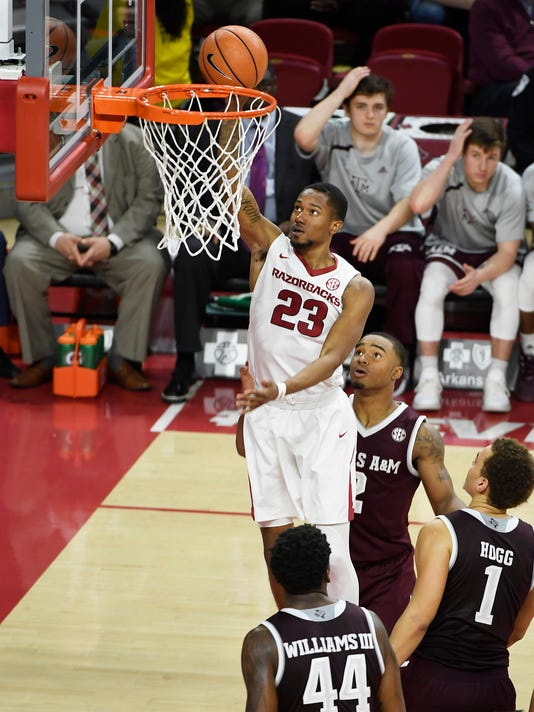 Arkansas guard C.J. Jones drives past Texas A&M defenders TJ Starks (2), DJ Hogg (1) and Robert Williams (44) to score during the first half of an NCAA college basketball game Saturday, Feb. 17, 2018, in Fayetteville, Ark. (AP Photo/Michael Woods)