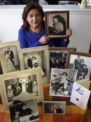Cynthia Rodriguez poses with pictures of her mother, Elfida P. Chavez Romero, who died of natural causes Nov. 5. Romero was 90.