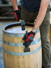 Tony Fletcher tightens the staves on a barrel at Green Mountain Grain & Barrel in Richmond on Thursday, May 24, 2018.