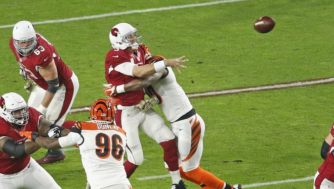 Cardinals' quarterback Carson Palmer throws while being hit by Bengals' Michael Johnson in the first half on Nov. 22, 2015 in Glendale, Ariz.