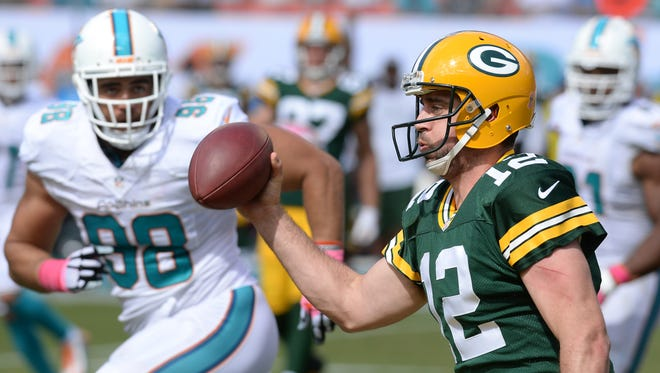 Green Bay Packers quarterback Aaron Rodgers (12) pump fakes with the ball on a scramble against the Miami Dolphins at Sun Life Stadium.
