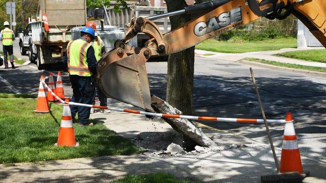 A backhoe lifts park of the sidewalk as employees with Suez check water service lines, goosenecks and pipes on Edgewater Road in Cliffside Park on Thursday May 2, 2019.