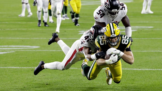 The Packers' Robert Tonyan (85) goes in for a touchdown as he is being tackled by the Atlanta Falcons' Sharrod Neasman (41) and Foye Oluokun (54) during the first half of a game Monday night in Green Bay, Wis.