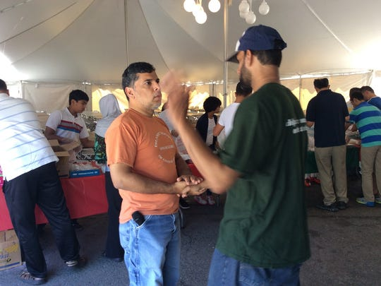 Mujibur Rehman (left), a member of the board of trusees of the Islamic Society of Central Jersey, greets another member of the mosque as about 300 volunteers gather to prepare 1,500 meals for hungry people in New Jersey.